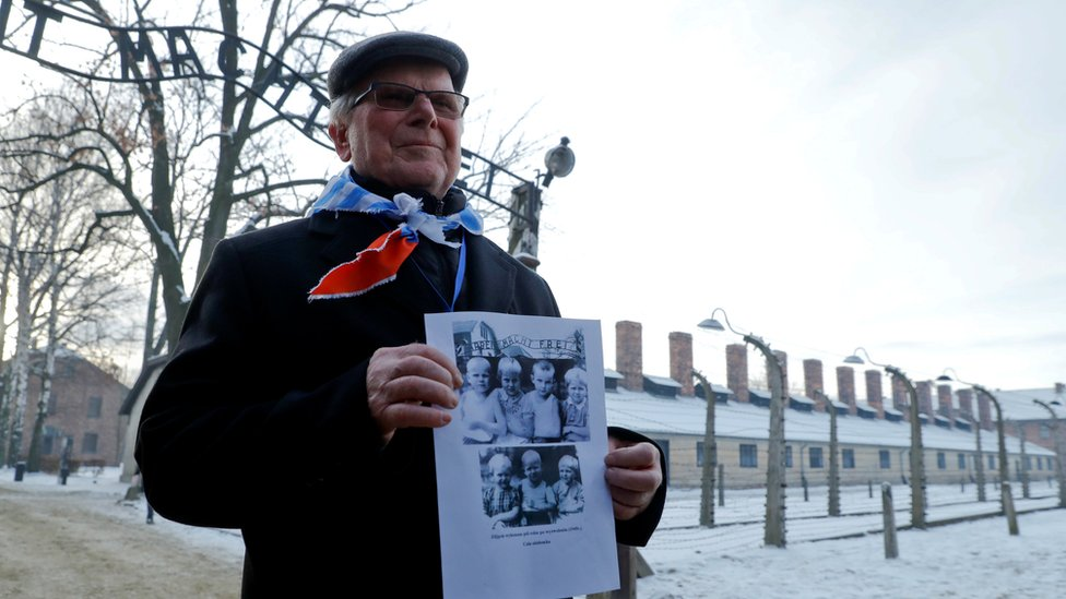 A survivor holds a poster at the former Nazi German concentration and extermination camp Auschwitz, as he attends ceremonies marking the 74th anniversary of the liberation of the camp and International Holocaust Victims Remembrance Day, in Oswiecim, Poland