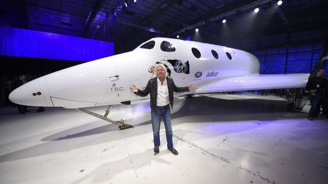 Sir Richard Branson poses in front of his new Virgin Galactic Spaceship