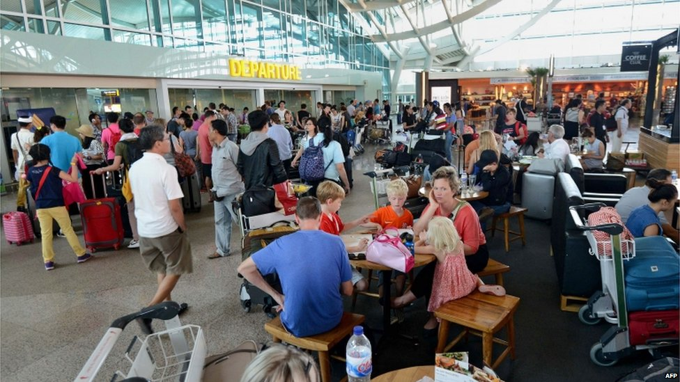 Passengers sit around the international terminal at Bali's Ngurah Rai airport in Denpasar waiting for information of flight delays due to volcanic ash near Indonesia's resort island on 10 July 2015.