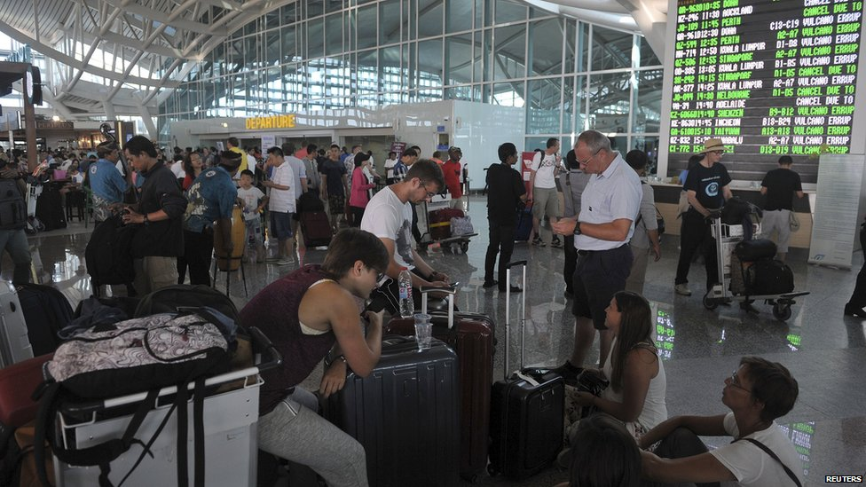 Passengers wait for information at an airport in Bali