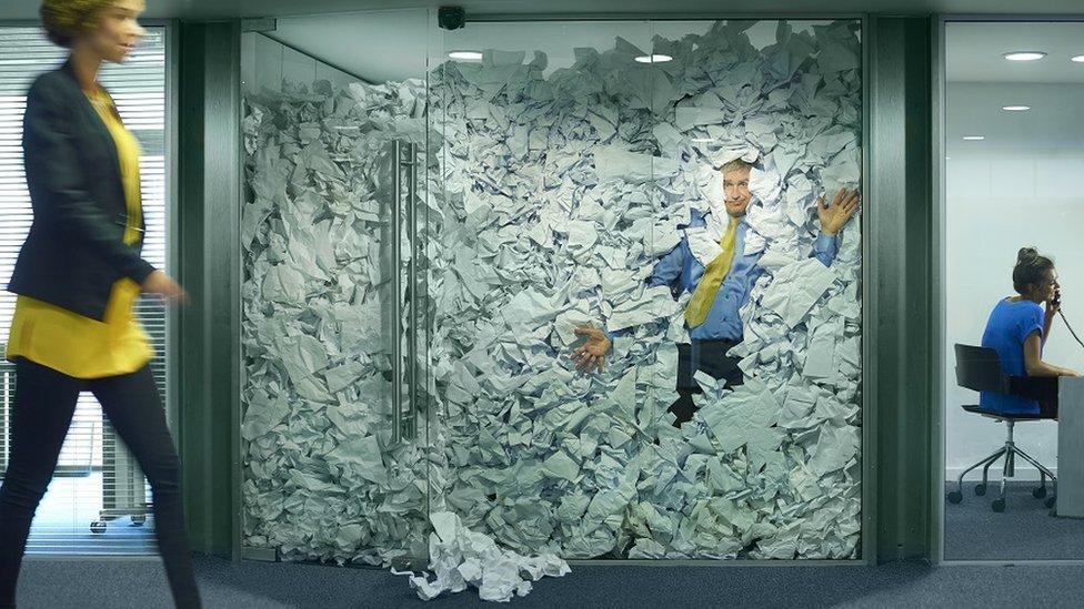 Un ejecutivo trapado en una oficina con paredes de cristal en medio de papeles.