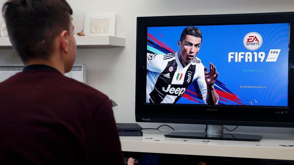 Un joven se prepara para jugar FIFA