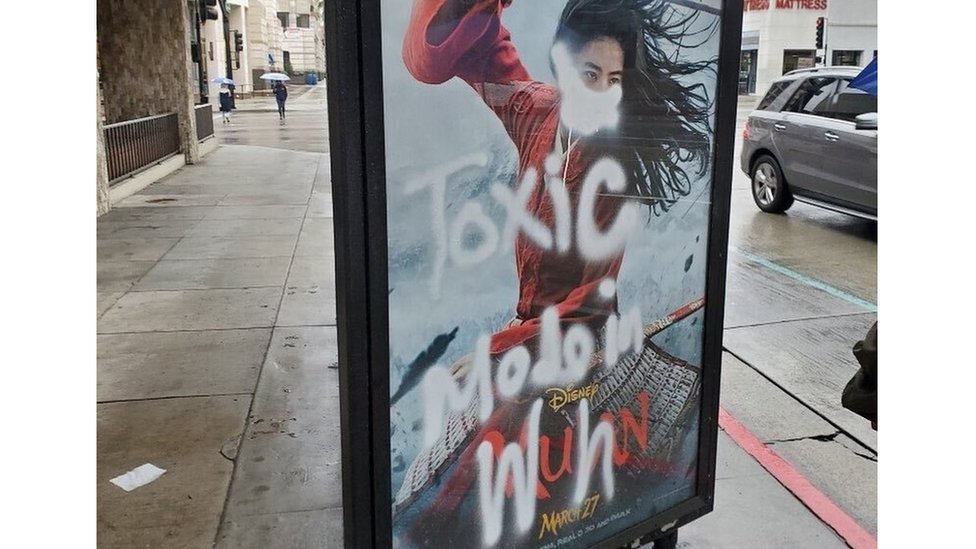 "A Mulan film poster defaced with graffiti - a mask is painted over her face, along with the words ""toxic made in Wuhan"""