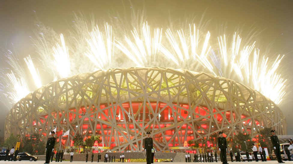 Fireworks light up the sky as paramilitary policemen stand guard outside the National Stadium during the Opening Ceremony for the Beijing 2008 Olympic Games