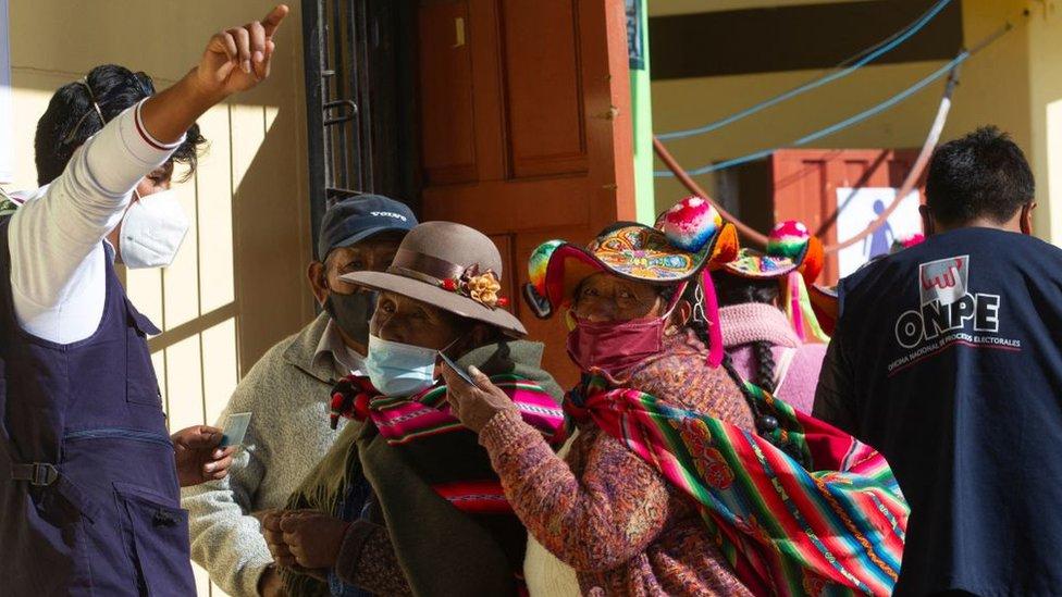 Indígenas peruanos reciben indicaciones en un centro de votación.