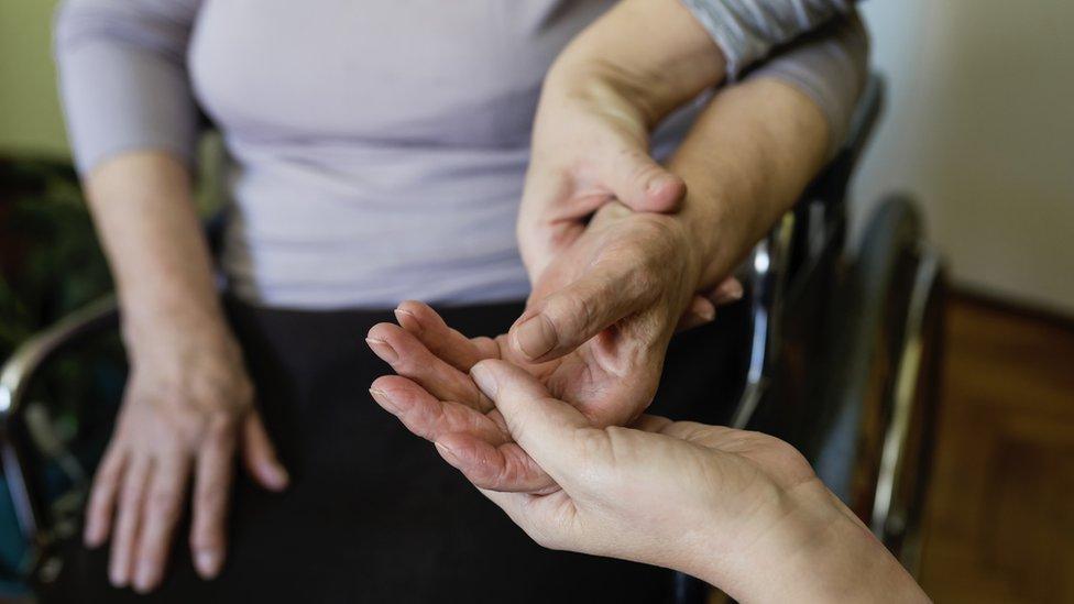 Una terapeuta manipula la mano de una mujer en silla de ruedas