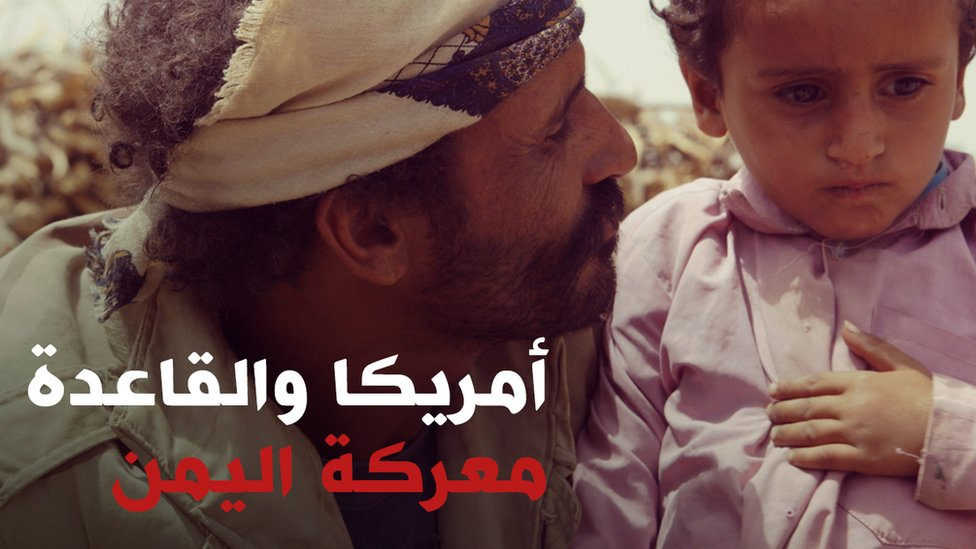 رجل يمني ينظر إلى ابنه الصغير
