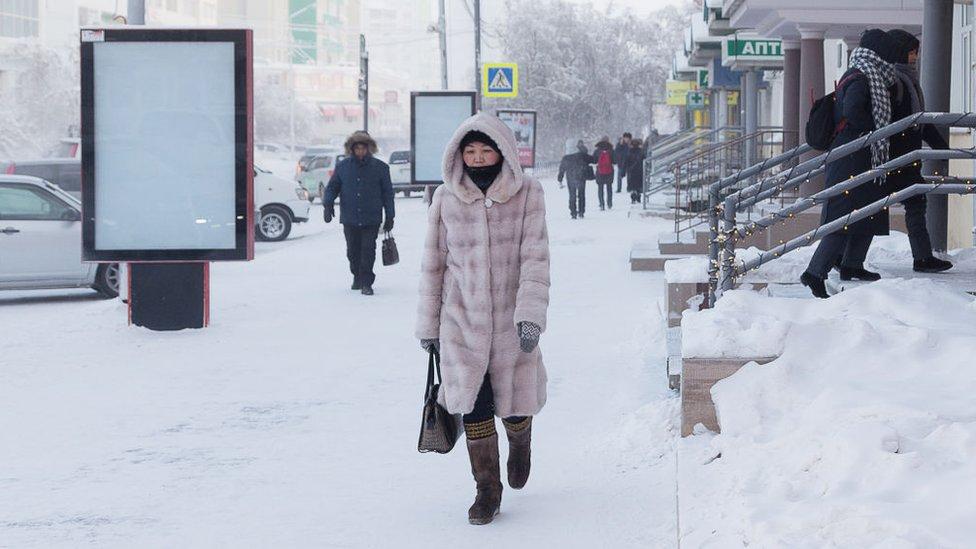 Woman walk trough the snow in Yakutsk