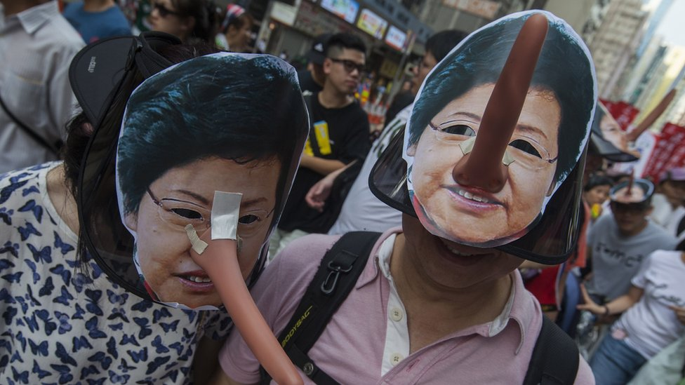 """Protesters wearing masks of Hong Kong Chief Executive Carrie Lam, complete with a long """"Pinocchio"""" noses to suggest lying, march through the streets during the annual pro-democracy march, Wan Chai, Hong Kong, China, 01 July 2018."""