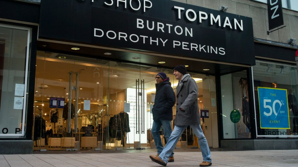 Two men walk past an Arcadia Group sign