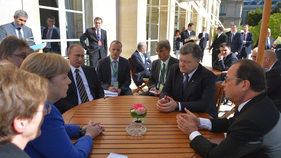 (L-R at table) German Chancellor Angela Merkel, Russian President Vladimir Putin, Ukrainian President Petro Poroshenko and French President Francois Hollande attend a meeting on Ukrainian crisis at the Elysee Palace in Paris