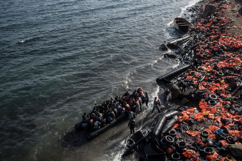 Life jackets abandoned on beach as another dinghy of people reaches shore