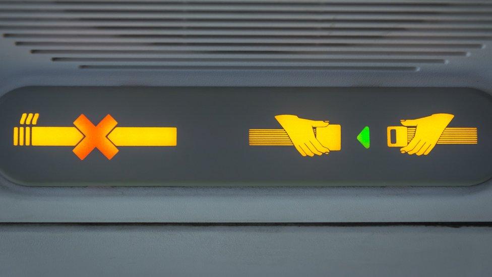 Cartel luminoso de no fumar y de abrocharse el cinturón de seguridad.