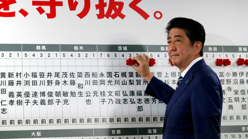 Prime Minister Shinzo Abe looks on as he puts a rosette on the name of a candidate who is expected to win the lower house election