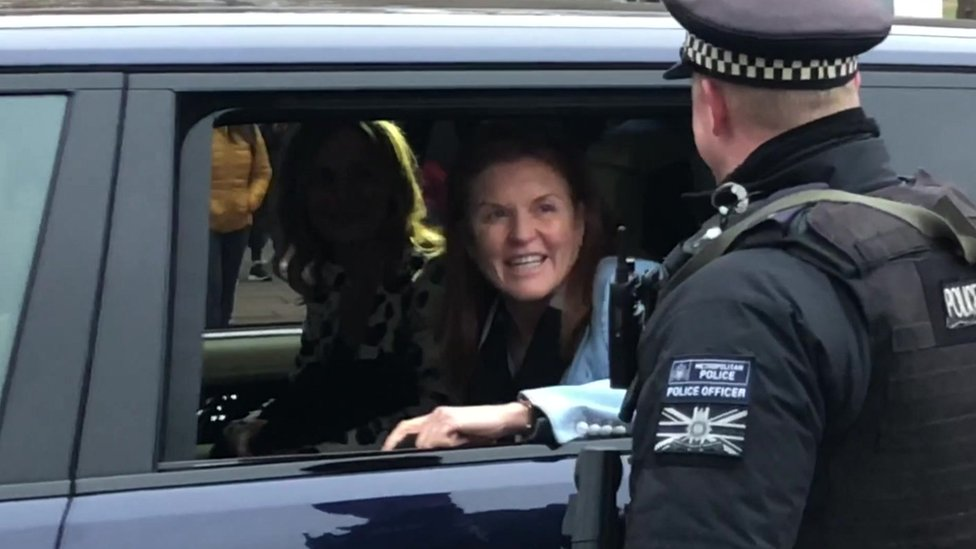 Sarah Ferguson in a car being driven into the grounds of Buckingham Palace