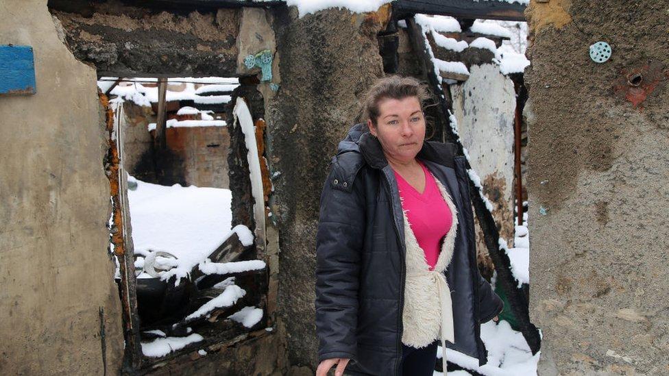 سيدة تقف خارج منزلها الذي دمرته قذيفة بالقرب من دونيتسك