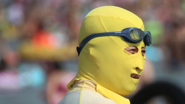 A person wearing a yellow 'facekini' - a face covering to protect from the sun
