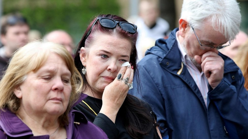 MEMBERS OF THE PUBLIC cry outside the funeral