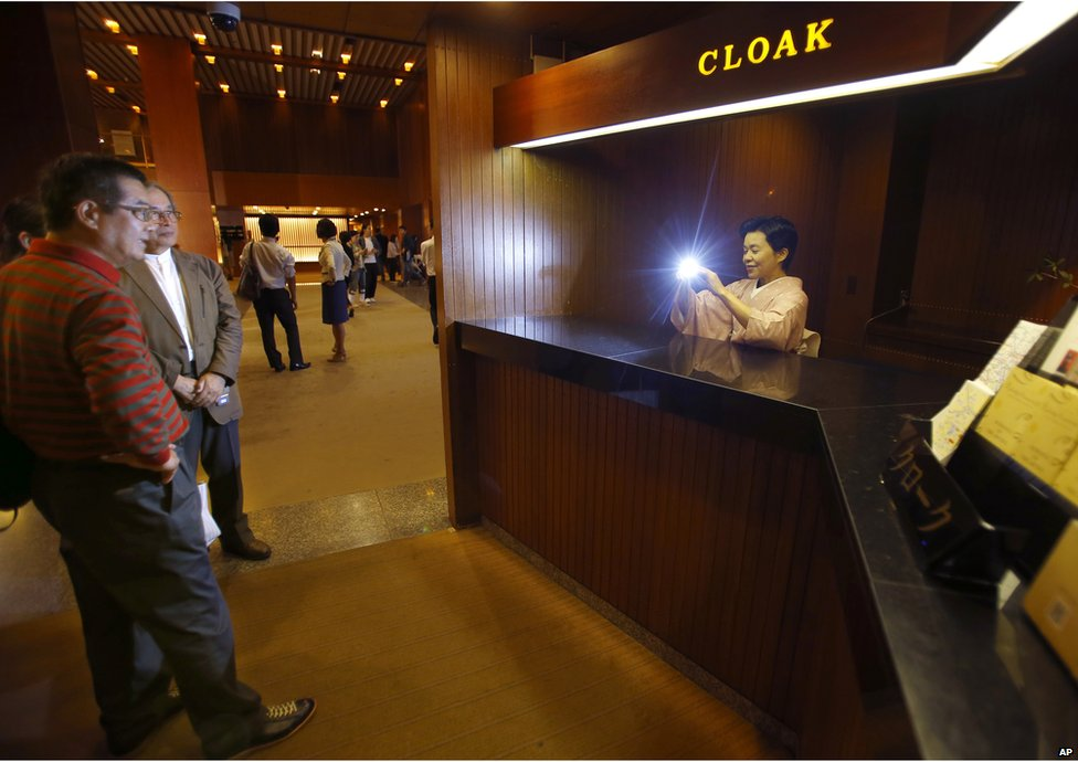 An employee takes a photo of visitors at the main lobby of Hotel Okura in Tokyo, Monday, 31 August 2015.