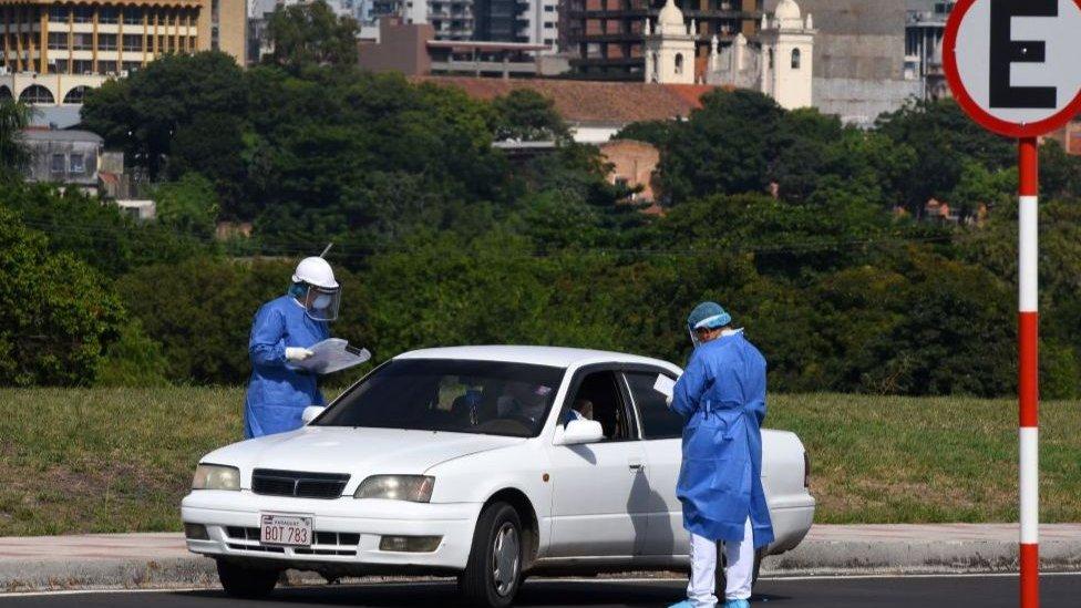 Profissionais de saúde checam pessoas que cruzam a fronteira com o Brasil