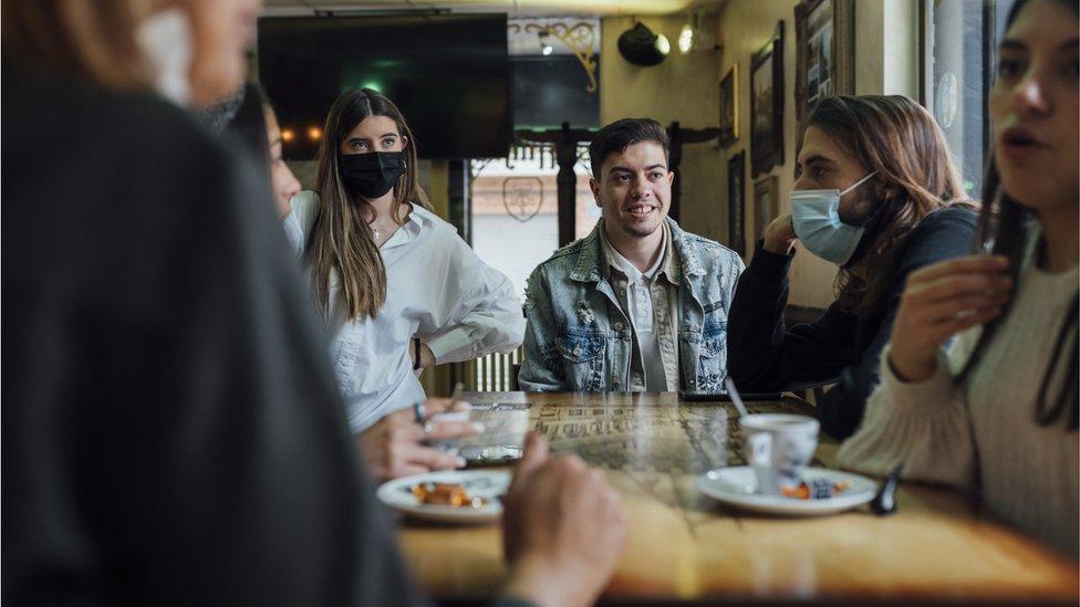 Grupo de jovens sentados ao redor de uma mesa
