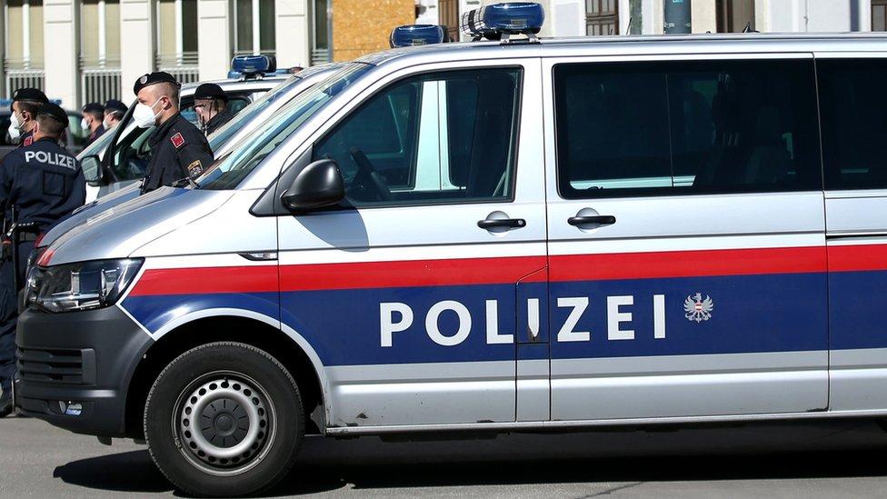 Viatura da polícia austríaca, com agentes ao lado