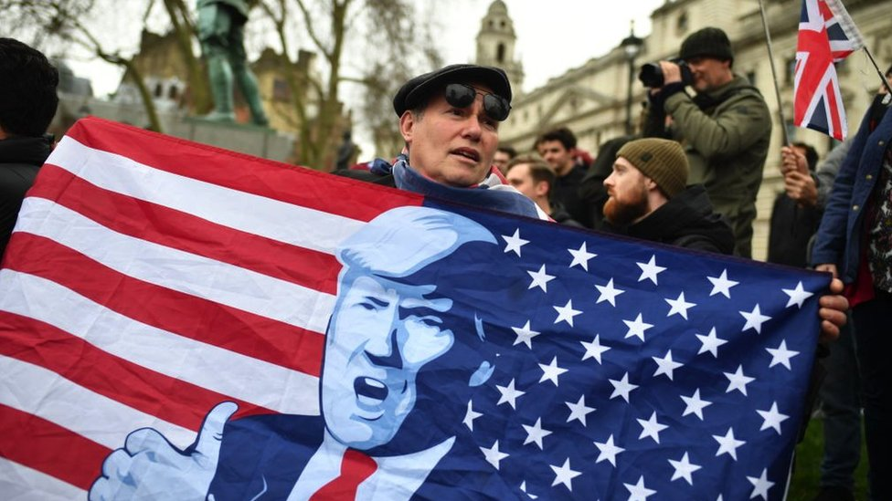 A Brexit supporter holds up a flag, inspired in the American flag, with Trump's face on it, as the UK counted down to exit the EU on 31 January 2020 in London