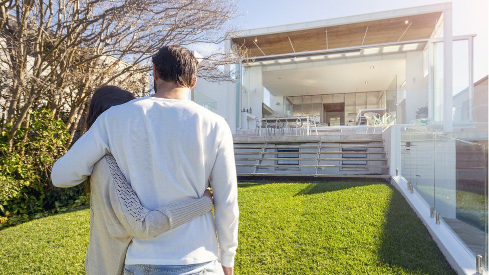 Couple looking at big house