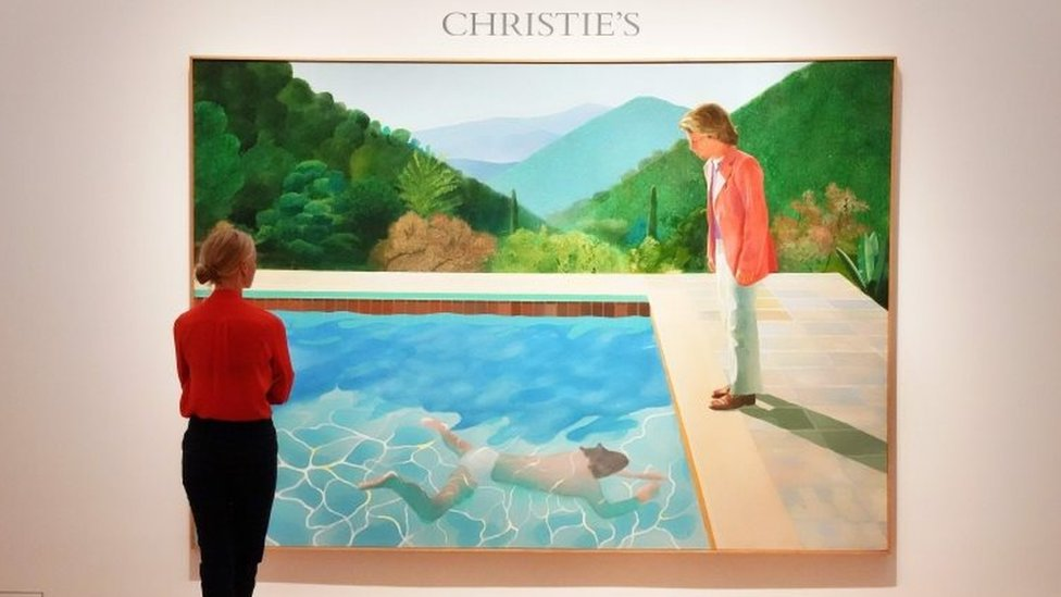 """A woman looks at David Hockney's """"Portrait of an Artist (Pool with Two Figures)"""" during a press preview on September 13, 2018 at Christie's New York."""