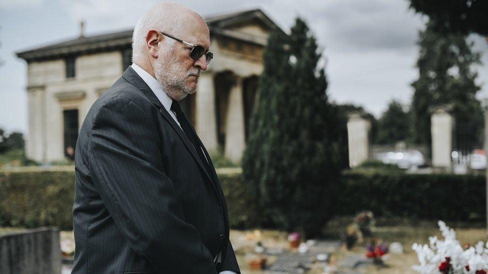 Hombre frente a una tumba.