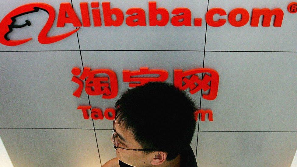 Man walks in front of an Alibaba logo