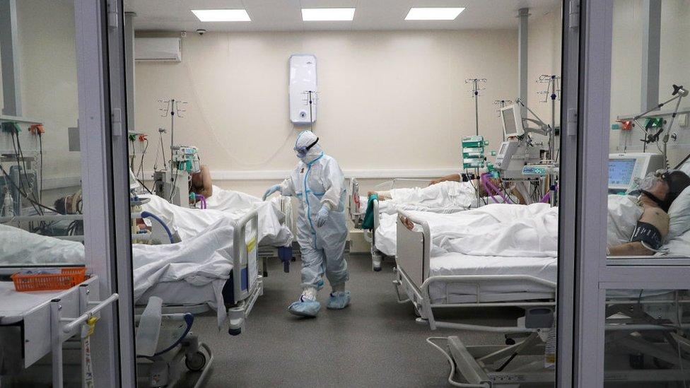 Pacientes con covid-19 en un hospital con un médico totalmente protegido.