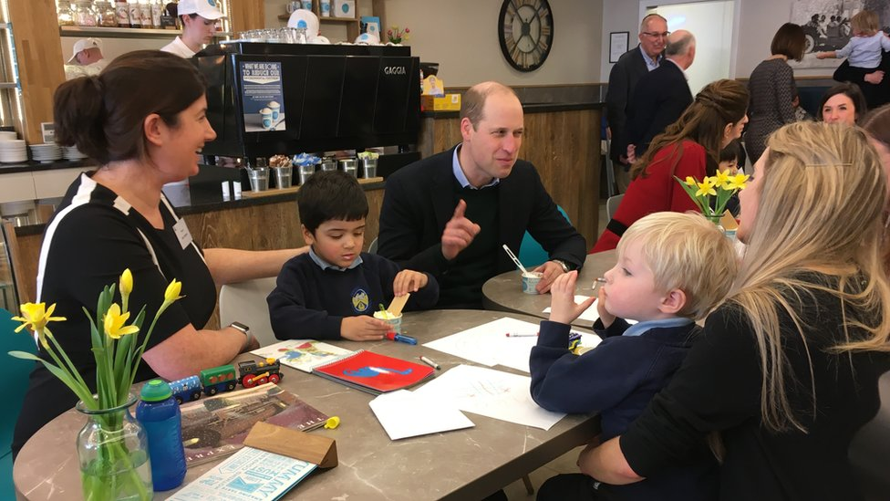Prince William enjoys an ice cream while talking to parents