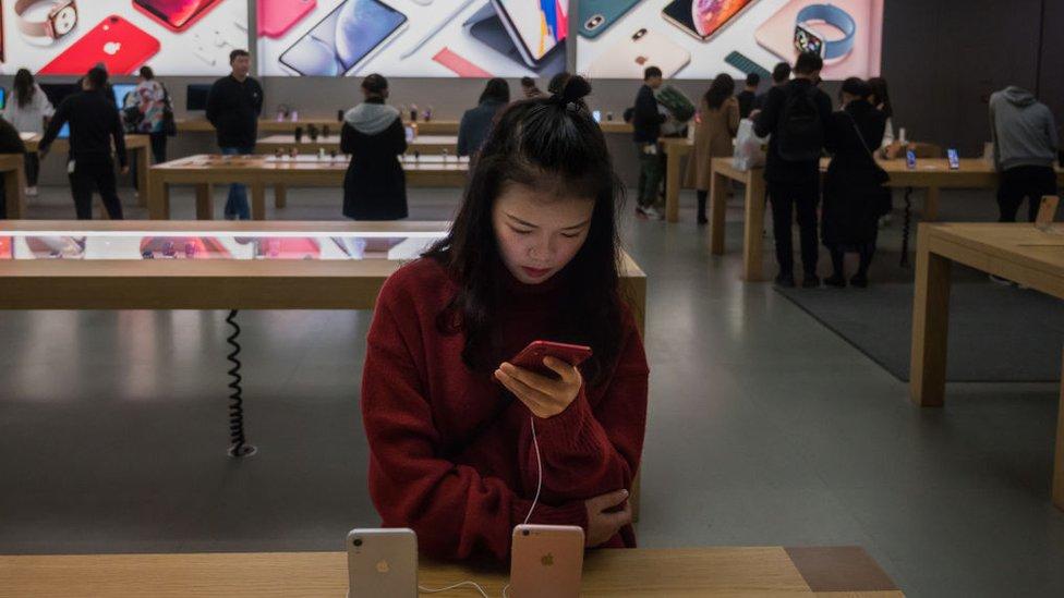 Una joven china mira un iPhone en una tienda de Apple en la ciudad sureña de Shenzhen.