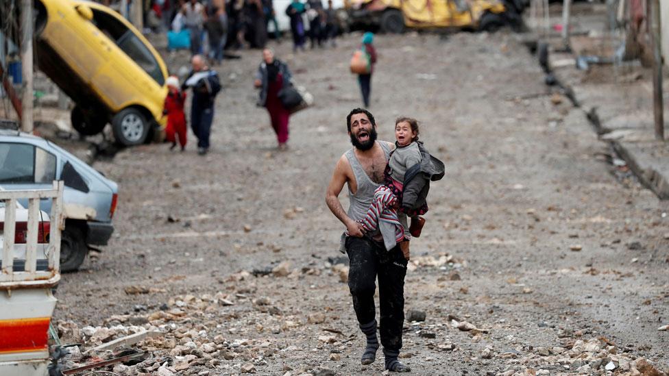 أب وابنته يهربان من معركة شهدتها مدينة الموصل العام الماضي