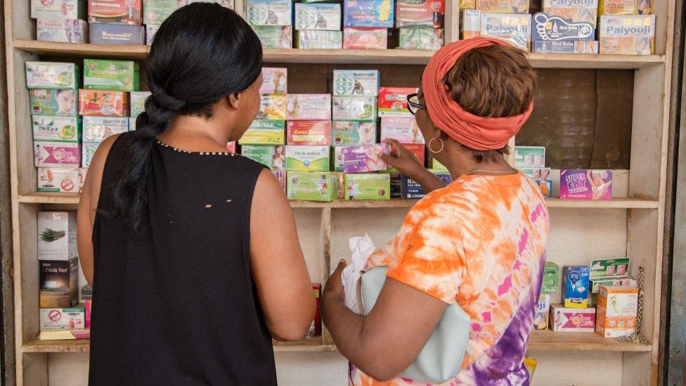 Dos mujeres miran un estante con productos de medicina tradicional.