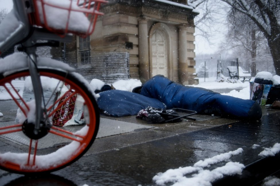 A man in a sleeping bag sleeps in the snow