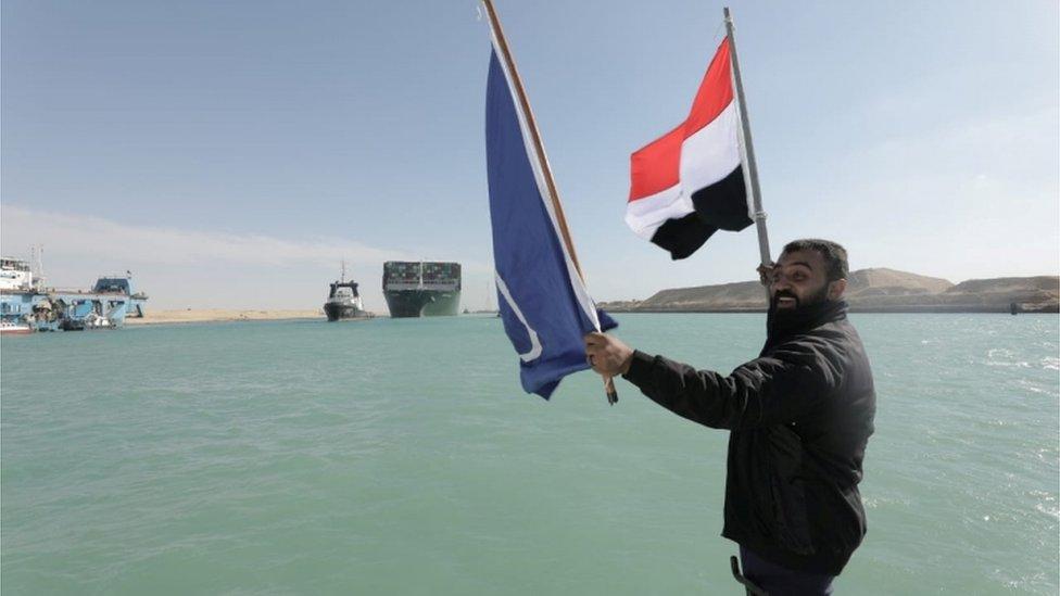 رجل يلوح بالعلم المصري لدى مشاهدته سفينة إيفر غيفن تبحر في قناة السويس بعد تعويمها.