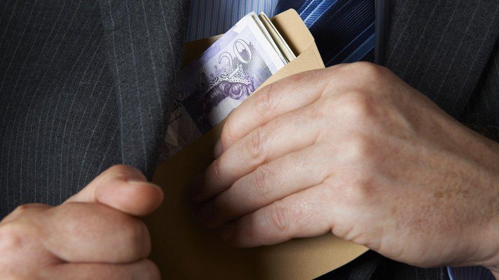 Un hombre saca billetes del bolsillo