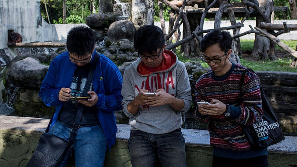 Young people on their phones in Yogyakarta Indonesia, 2016