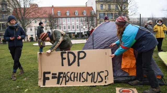 Manifestantes con un cartel en el que atacan al FDP.
