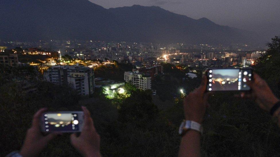 Personas tomando fotos a Caracas a oscuras con sus teléfonos.