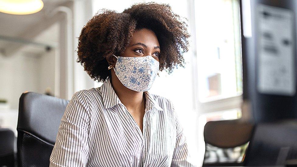 Mulher negra no escritório com máscara