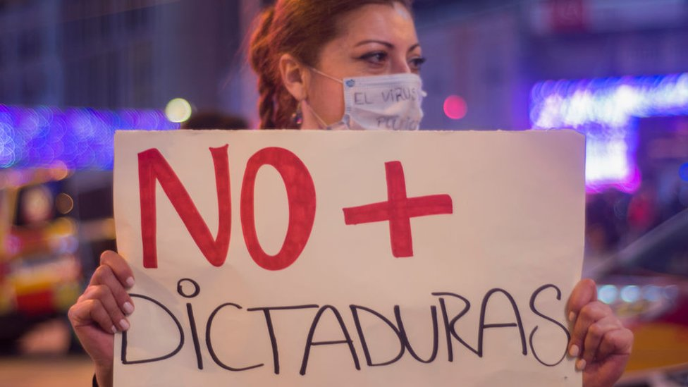 """Woman in Madrid protesting with sign reading """"No to dictatorship"""""""