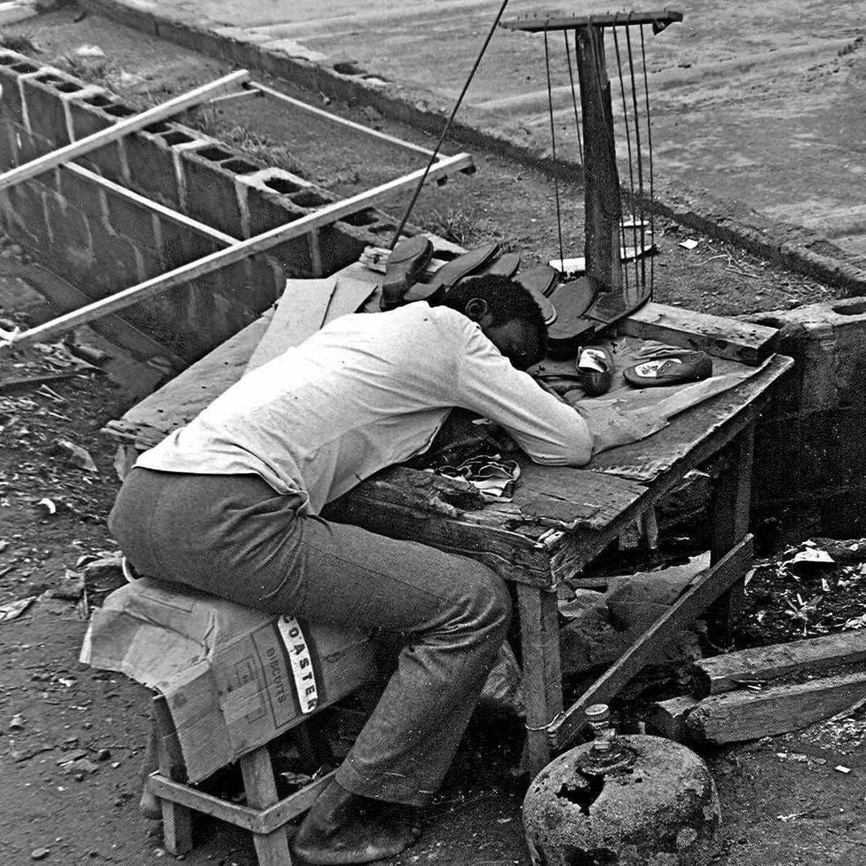 "A photo by Sunmi Smart-Cole entitled: ""Wake Up, Nigeria"" - 1984, a man a cobbler asleep on his work bench"