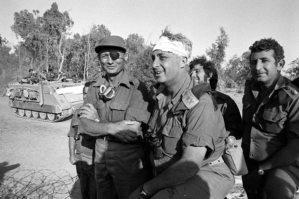 موشيه ديان، وزيرالدفاع الإسرائيلي، على اليسار، وعلى يمينه أرئيل شارون ، قائد الفرقة 143 الإسرائيلية، يقفان على الأراضي المصرية من الضفة الغربية للقناة بعد تمكن فرقة شارون، بدعم أمريكي، من فتح ثغرة بين الجيشين الثاني والثالث المصريين في سيناء. وكان شارون ، الذي أصبح لاحقا رئيس وزراء إسرائيل، قد أصيب في المعركة.