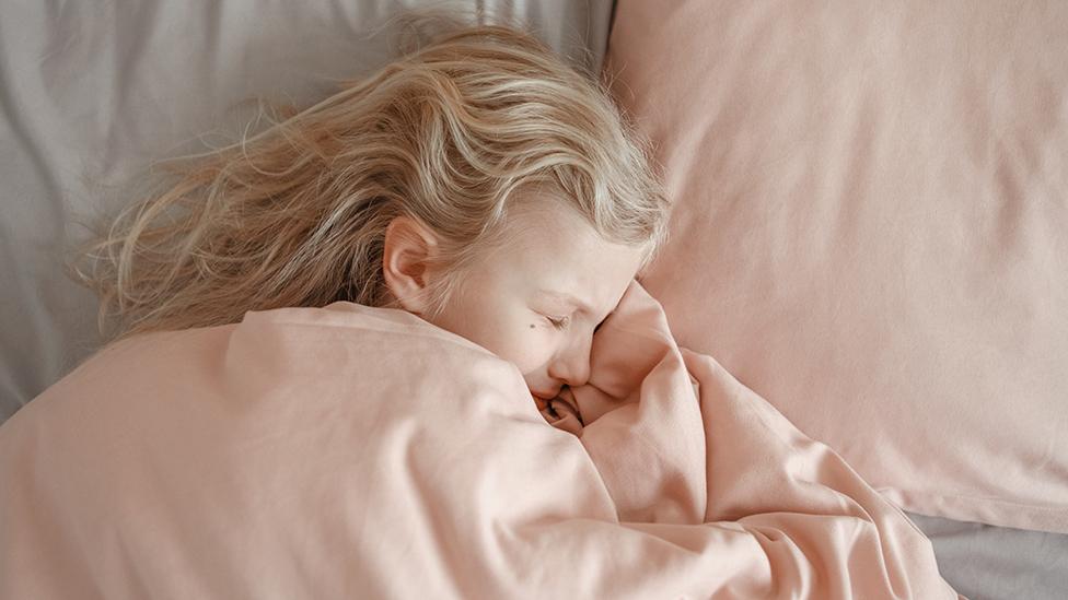 Una niña durmiendo con cara de sufrimiento