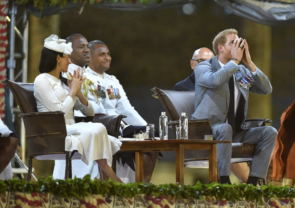 Prince Harry drinks kava as his wife Meghan, the Duchess of Sussex looks on at a traditional welcome ceremony after they arrived in Suva, Fiji on October 23, 2018