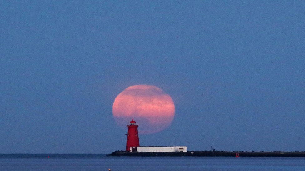 The final supermoon of the year rises over Poolbeg Lighthouse in Dublin Bay, Ireland