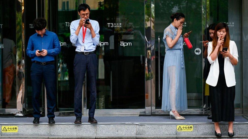 Gente fumando afuera de un centro comercial en Beijing.
